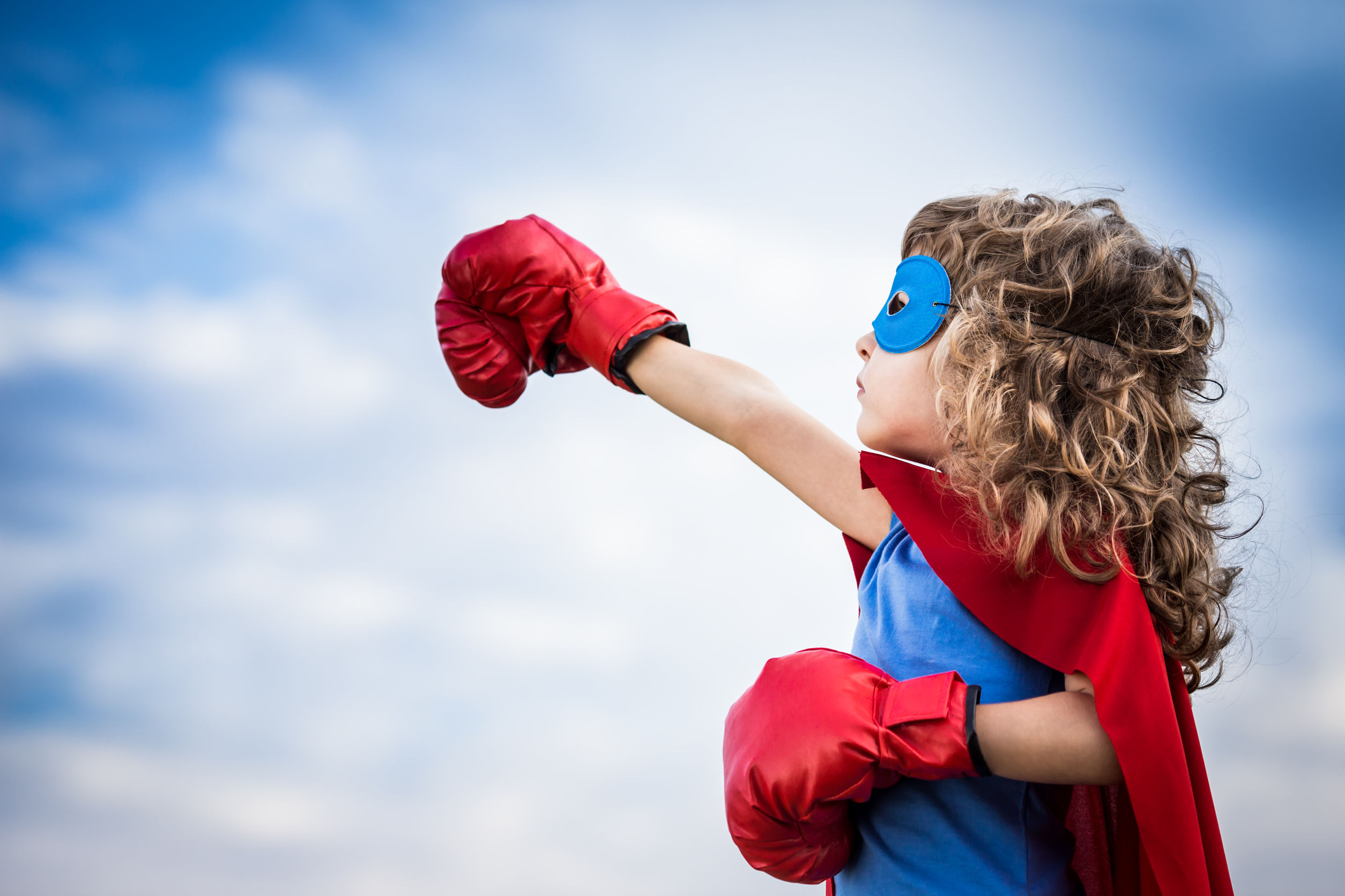 26818997 - superhero kid against summer sky background. girl power and feminism concept