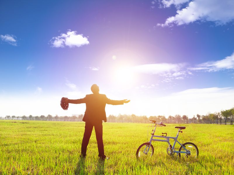 24871220 - businessman relaxing in green land and sun with bicycle